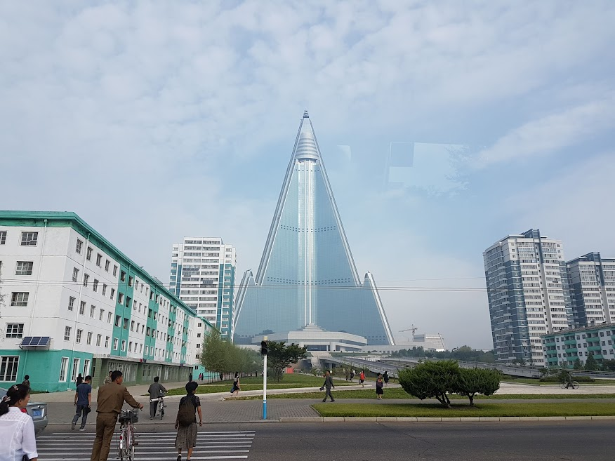 People going about their day, with Ryugyong Hotel on the horizon