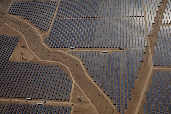Photo aérienne d'une vaste installation solaire dans un paysage désertique