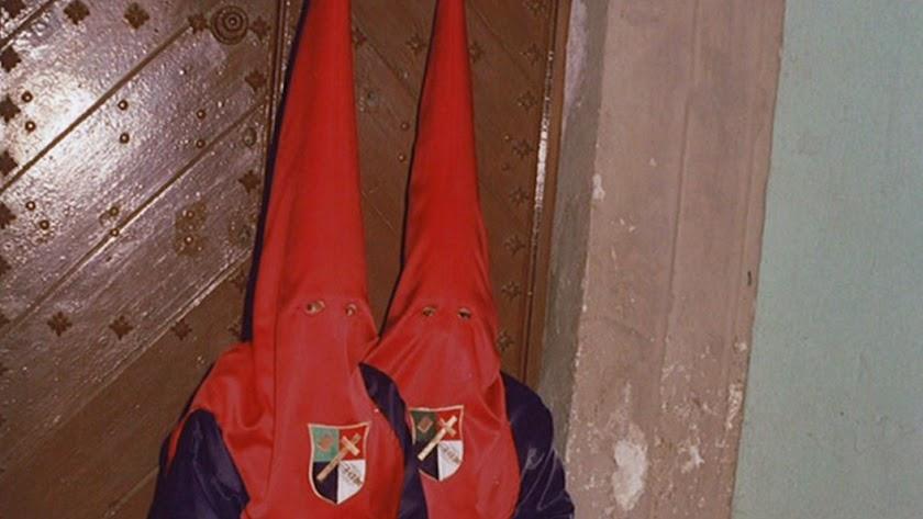 En la foto, dos penientes de la cofradía de Estudianates sentados en un tranco.