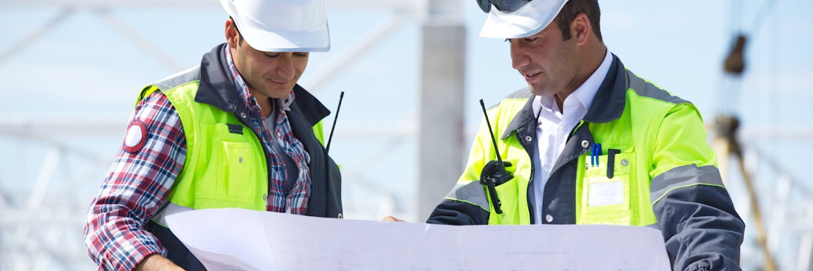 two male contractors wearing white helmets looking at a large blueprint of a building