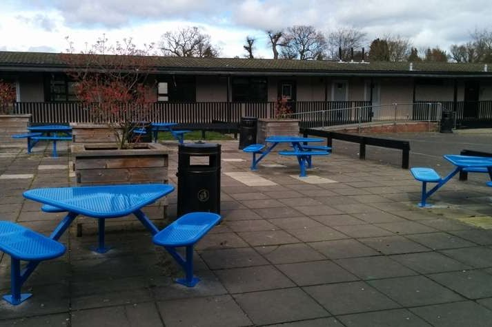 Triangular perforated steel picnic tables painted blue