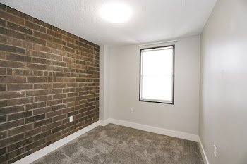 One Bed bedroom with brick accent wall and carpet