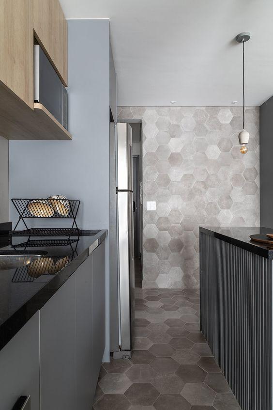 cozinha em estilo industrial com luminária pendente, revestimento hexagonal nas paredes e no piso na cor cinza, armários cinza e bancadas de granito preto