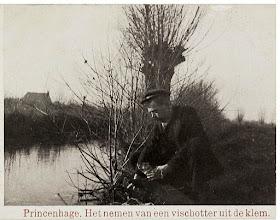Photo: 1930-1935 Man op oever van een stroompje neemt otter uit klem