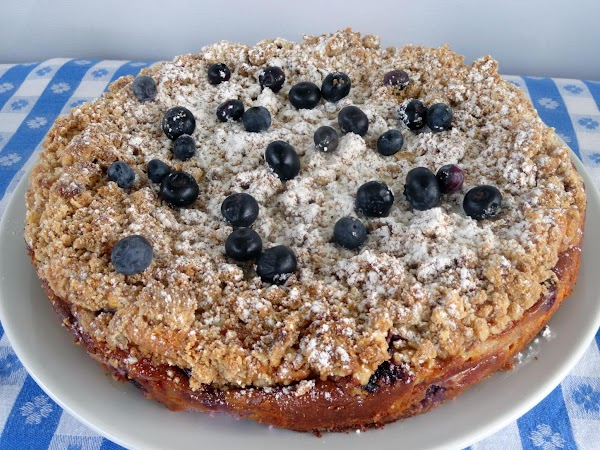 Sprinkle top of cake with powdered sugar, 1/4 cup blueberries, and place on cake...