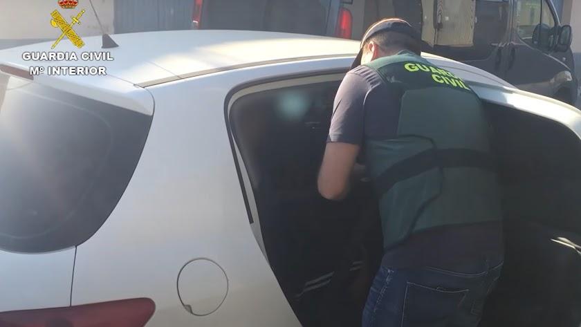 Un agente introduce a un acusado en el coche