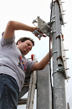 Photo: Garth VE4GWB mounting the plate for the 4 bay antenna on the structure