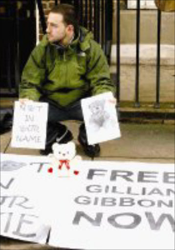SUPPORTER: A protester holding placards and a teddy bear sits outside the Sudanese Embassy in London on Saturday., to protest the 15-day [rospm term given to British school teacher, Gillian Gibbons. Pic. Max Nash. 01/12/07. © AP.