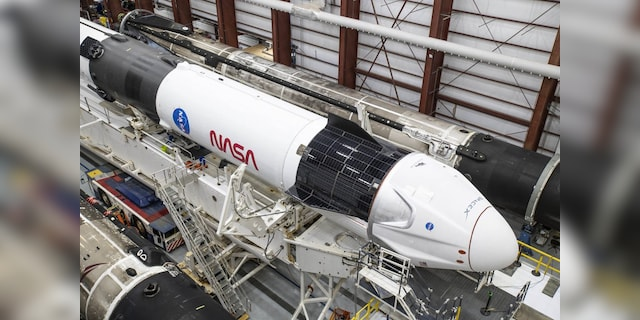 A SpaceX Falcon 9 rocket and Crew Dragon Resilience for NASA SpaceX's Crew-1 mission are seen inside the SpaceX Hangar at NASA's Kennedy Space Center in Florida on Nov. 9, 2020, before rollout to Launch Pad 39A. (Credit: SpaceX)