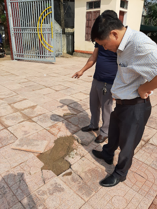 Viên gạch bị lốc lên làm lộ một lớp cát, không có lớp bê tông 10 cm