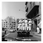 vrachtwagentje met politieagenten, waarvan er 4 achterin staan