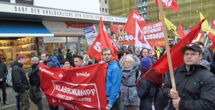 Demonstrant:innen mit (überwiegend) roten Fahnen und Transparenten.