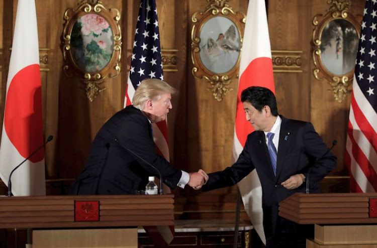 US President Donald Trump (L) shakes hands with Japan's Prime Minister Shinzo Abe. File photo