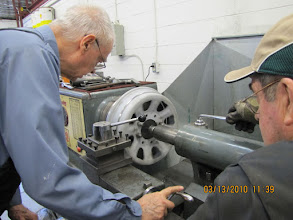 Photo: Ed and Duncan checking the setup on the Stanley lathe. The lathe is being used to remove the ice-cutter ridge on the CBL Wheels.  Photo courtesy of Ross Robinson.