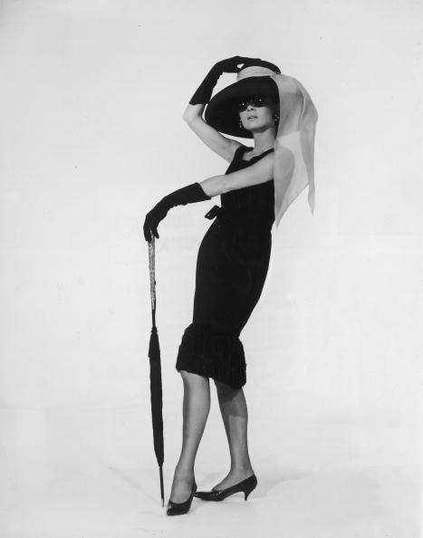 1961: Belgian-born actress Audrey Hepburn (1929 - 1993) in a black cocktail dress designed by French couturier Hubert de Givenchy in a promotional portrait for director Blake Edwards's film, 'Breakfast at Tiffany's'.