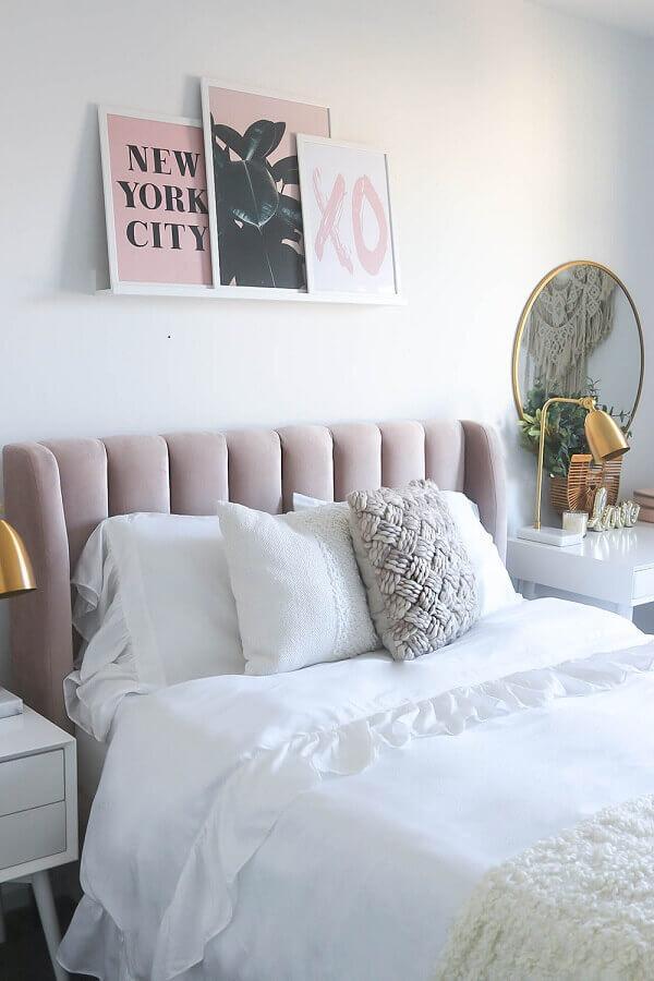 Quarto de casal com cabeceira aveludada na cor rosa, paredes brancas com quadros decorativos rosa e branco.