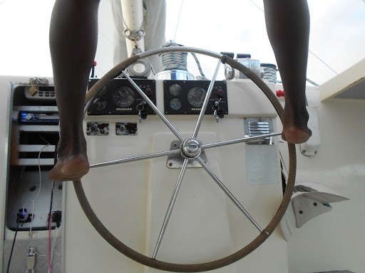 Cat captain steers with feet.JPG - The captain of our St. Kitts catamaran shore excursion steering with his feet