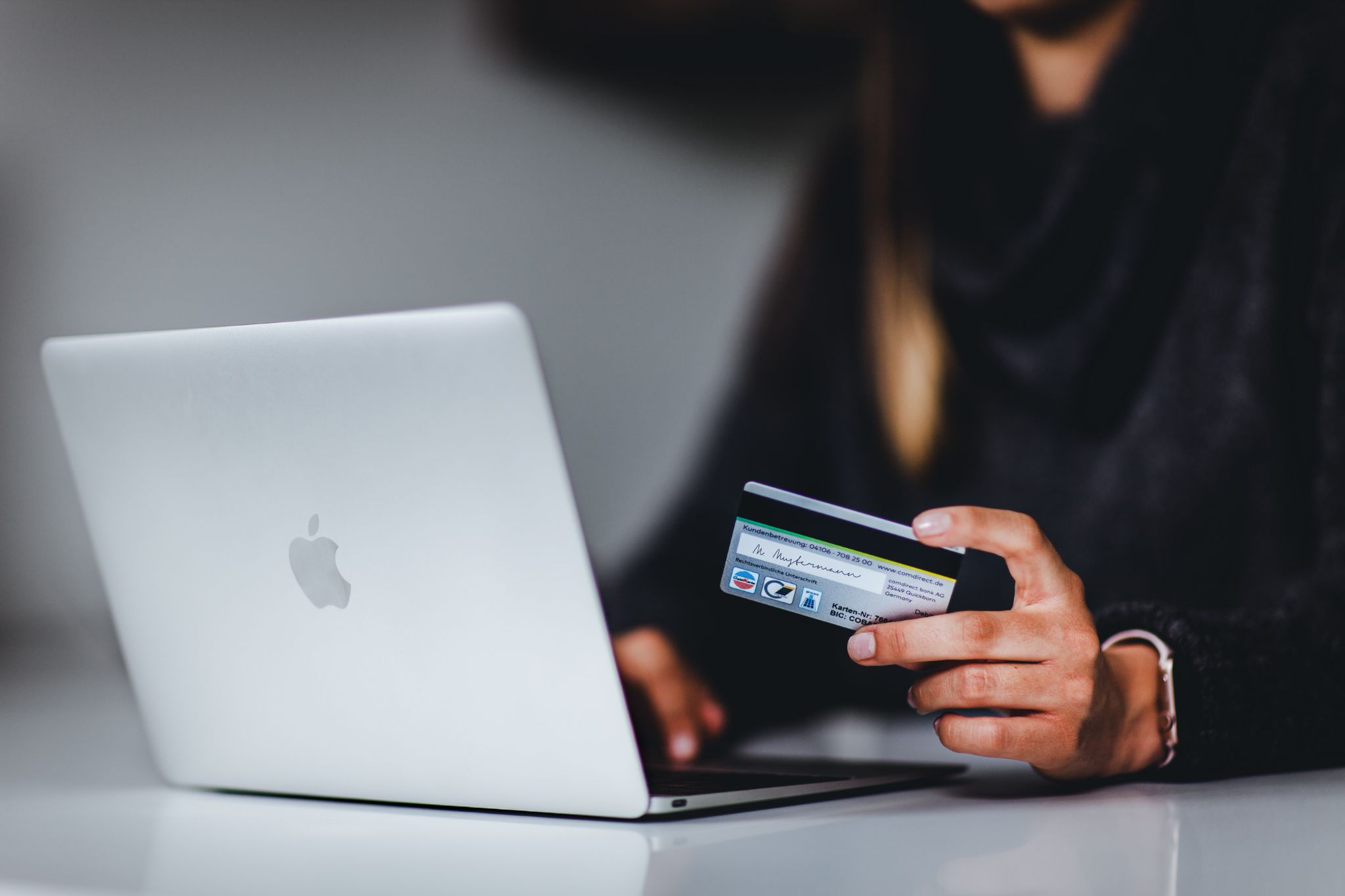 Woman in front of her laptop holding a credit card