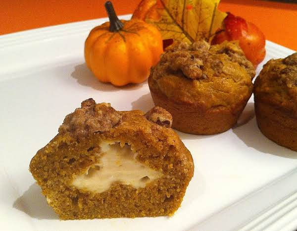 A Muffin Sliced In Half On A White Plate With Two Whole Muffins And A Couple Pumpkins.