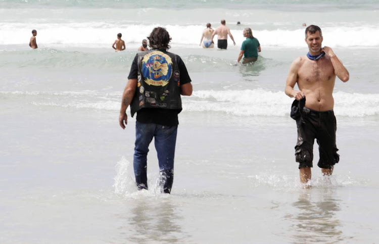 A biker wades into the water during a protest again the lockdown beach ban in Muizenberg on January 30 2021.