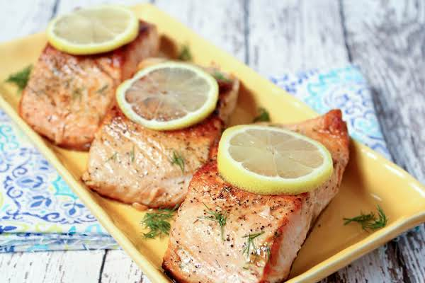 Three Pieces Of Salmon On A Plate With Lemon Slices.