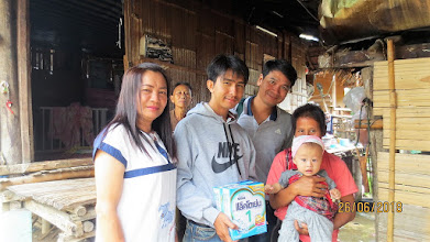 Photo: Arm, Gee and Daeng with baby Pong at home with his mum and grandmother.
