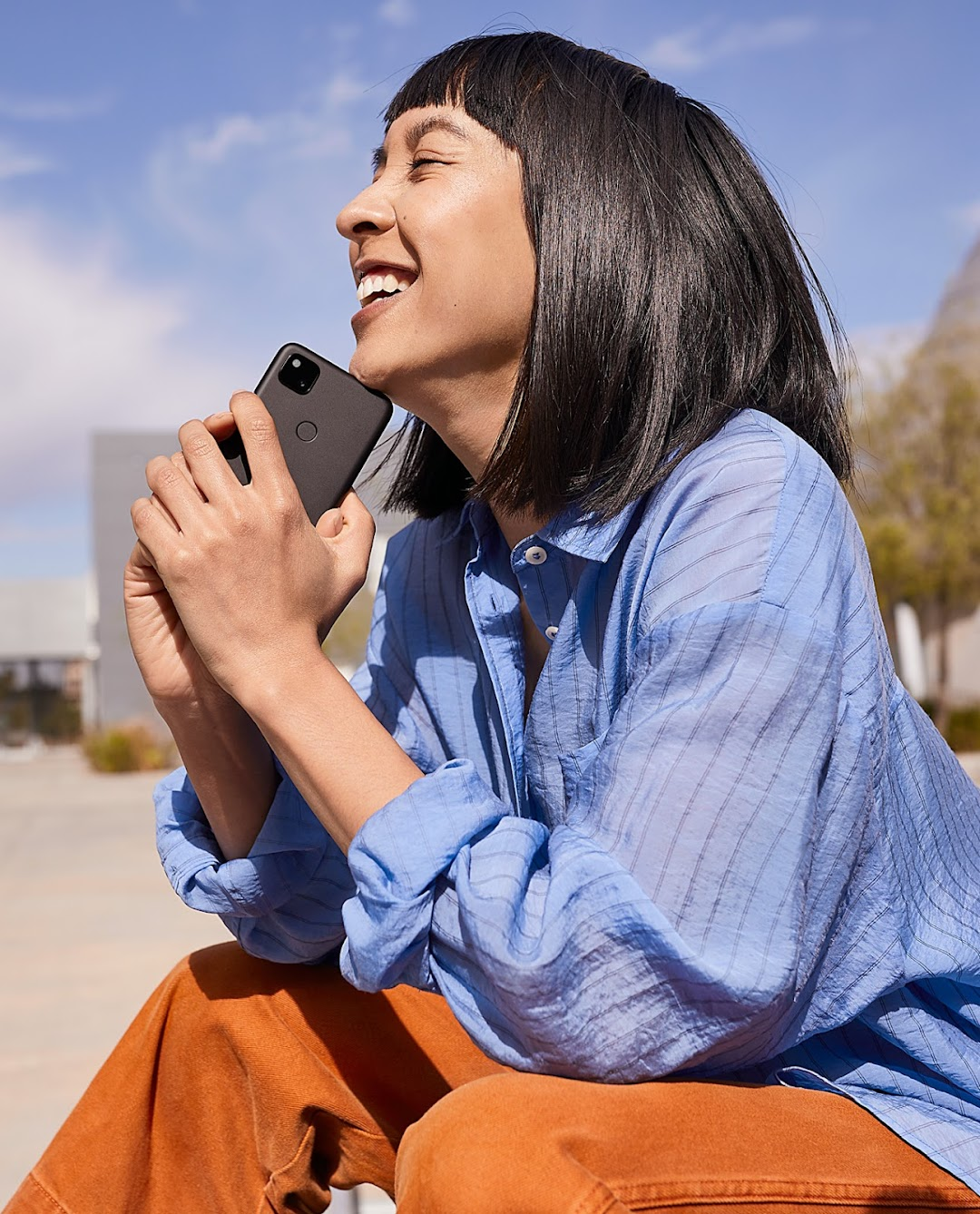 Woman smiling while sitting on the beach holding her Just Black Pixel.