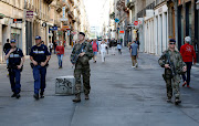 Police and army patrol the streets during the manhunt of a suspected suitcase bomber in central Lyon, France, May 25, 2019.
