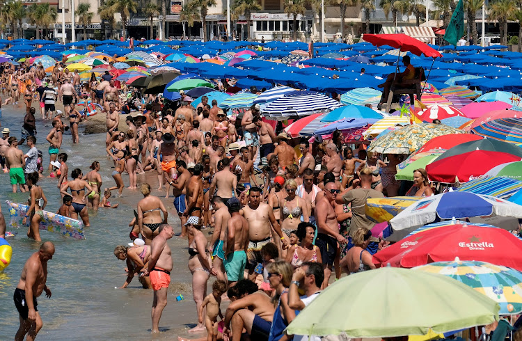People cool off at the beach during the heatwave in the southeastern coastal town of Benidorm, Spain.