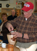 Photo: Bob Grudberg shows off his segmented urn and said that he found an easy way to turn threads, ...
