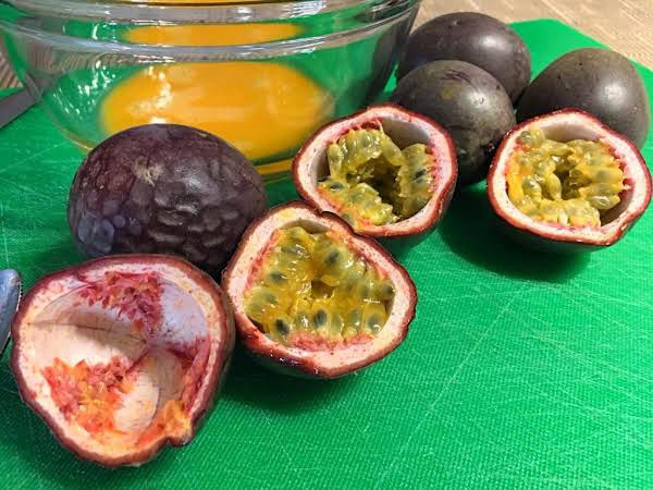 A Few Passion Fruits On A Green Cutting Board With A Glass Bowl Behind.