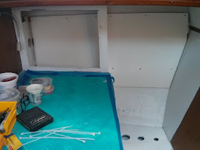 Photo: Holes for wire runs cut outboard of nav station seat (lower right). Once the wiring is complete, we plan to enclose this area with storage / arm rest.