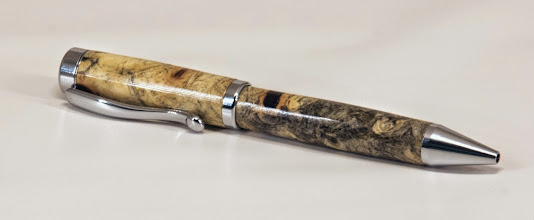 "Photo: Gary Guenther 5 1/2"" x 1/2"" pen [buckeye burl, Continental twist]"