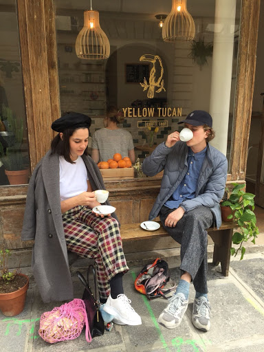 Yellow Tucan Coffee shop friends outside with coffee in Paris Le Marais