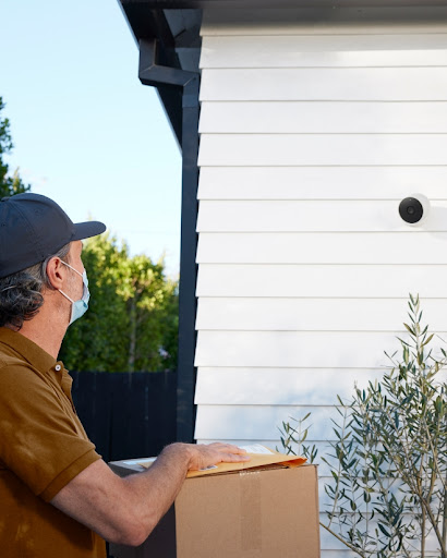 A delivery person is dropping a package off at a home.