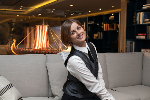 Viking-Star-bar-waitress - Bar server Ivana Vugovic next to a Viking ship replica in the Explorers Lounge on Viking Star.