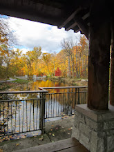Photo: Looking over Dogwood Pond at the colorful autumn leaves from under a wood and stone hut at Hills and Dales Metropark in Dayton, Ohio.