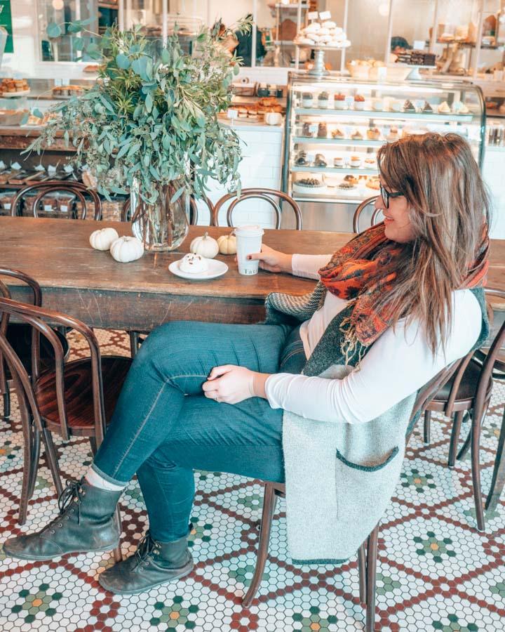 Lia trinkt in einer Kaffeestube in Boston in Jeans und Stiefeln.