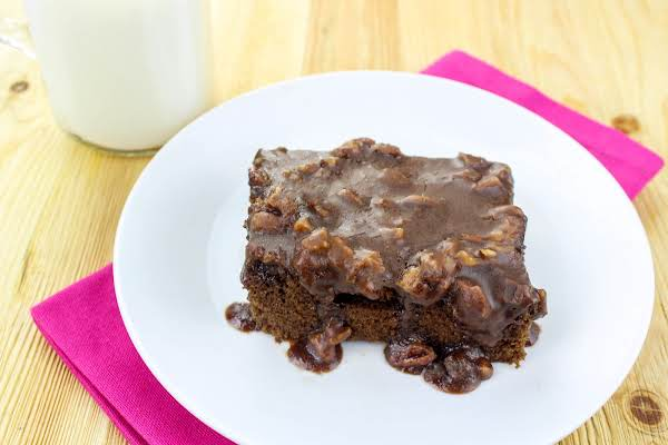 A Slice Of Chocolate Pecan Cake With Warm Gooey Frosting.