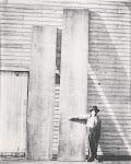 tegen een houten schuur staan 2 planken, een meter breed en 5 meter lang. Een man houdt arm gestrekt voor een plank om de breedte aan te geven