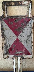Stark angerostetes steckbares Schild mit Griff und rot-weißem Symbol.