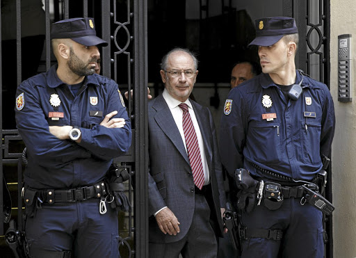 Denies wrongdoing:  Former IMF chief Rodrigo Rato, centre, walks between police officers as he leaves his office in Madrid in April 2015. He may not go to jail if he appeals against the ruling by Spain's National Court on Thursday. Picture: REUTERS