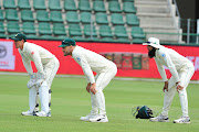 Batter-wicketkeeper Quinton de Kock (L) captain Faf du Plessis (C) and top order batsman Hashim Amla (R) fields in the slip cordon.