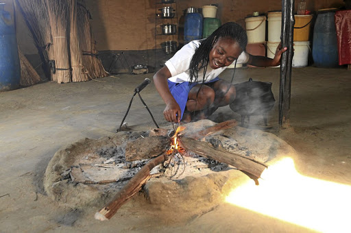 Snikiwe Xaba prepares the fire to warm her meal at home after school.