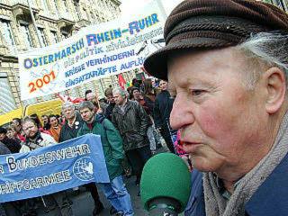 Jupp Angenfort mit Mikrofon, dahinter Demonstranten mit Transparent: «Ostermarsch Rhein-Ruhr 2001…».