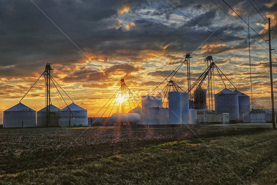 Bins and Silos at Sunset by Brian Kerls - Buildings & Architecture Other Exteriors ( stormy, milmine, building, farm land, illinois, central illinois, agriculture, storm clouds, landscape, agricultural, rustic, sun rays, farming, rural, weathered, country, farm, sky, grain bins, sun burst, sunset, silos, buildings, piatt county )
