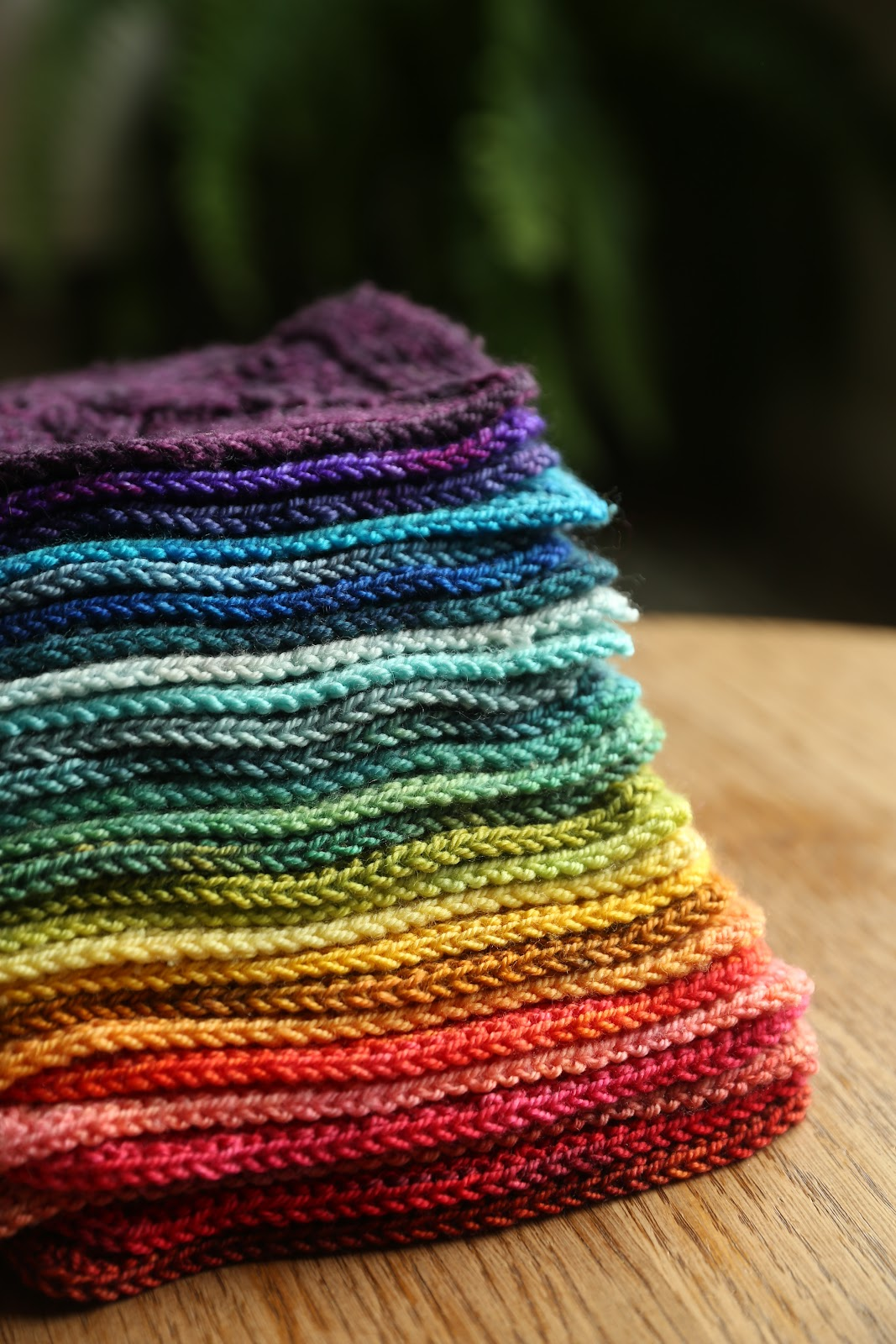 A rainbow stack of lace blanket squares.