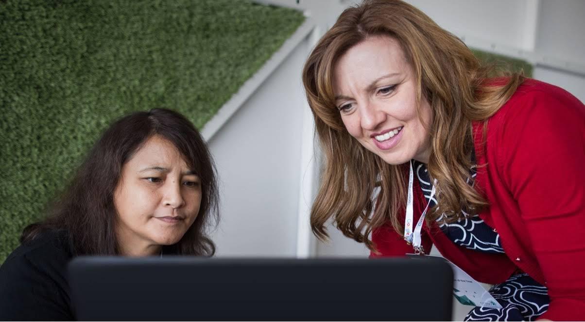 管理員坐在教育工作者旁邊,指導她在電腦上使用 G Suite