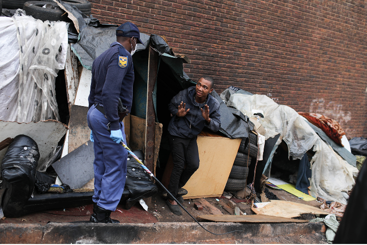 A policeman threatens a man in Hillbrow, Johannesburg, during the crackdown on people infringing the lockdown regulations.