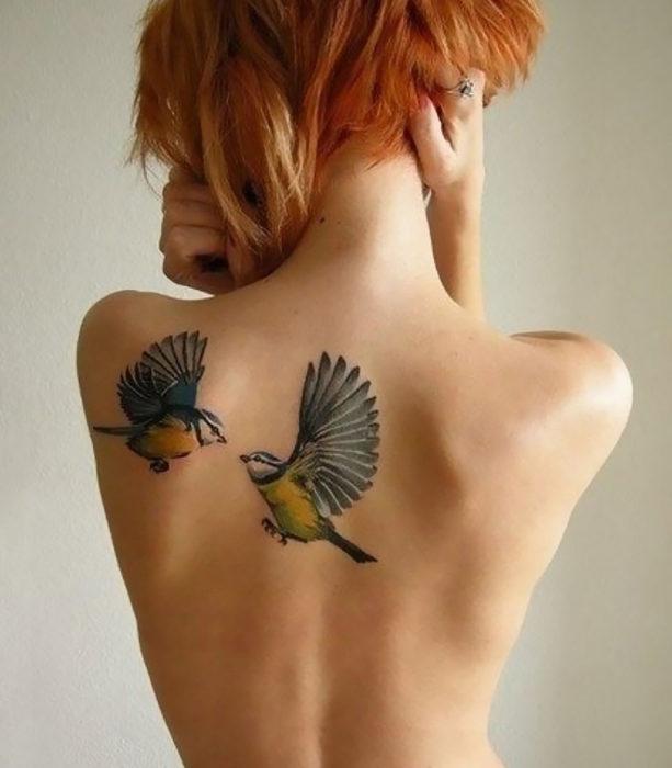 Tatuagem de dois pássaros nas costas da mulher
